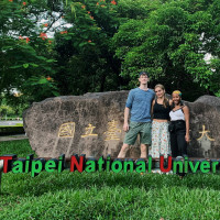 Students standing in front of the sign for Taipei National University of the Arts
