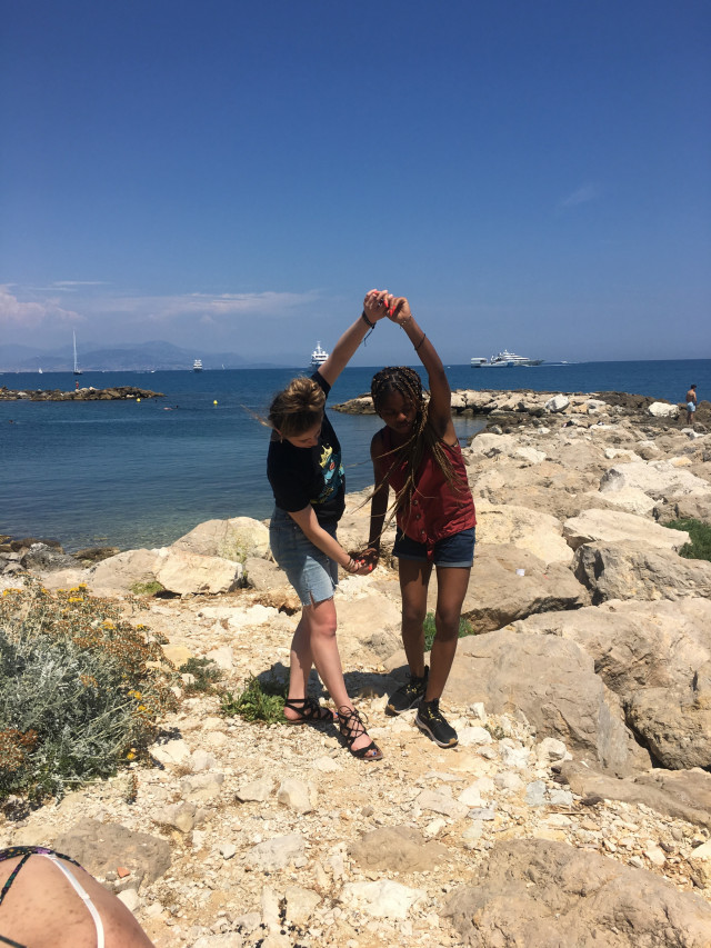 Students dancing on rocks, Antibes, France