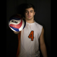 Photo of Nick holding a volleyball and wearing his Purchase team jersey.