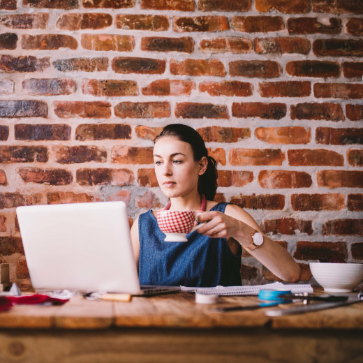 Young businesswoman working on laptop and drinking coffee
