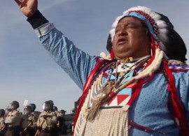 In October 2016, a tribal member offers a prayer in support of water protectors shortly before being arrested by militariz...