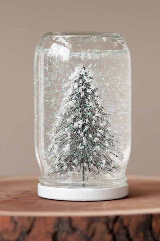 Mason jar with snow, water, and fake fur tree on wood