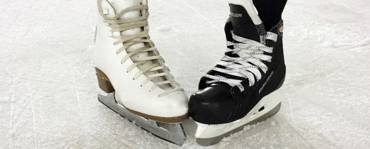 Figure skate and hockey skate on ice rink