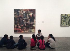A Neuberger Museum of Art docent speaks with a group of students about artwork by Louise Fishman