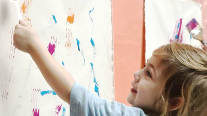 Image of a child artist creating a finger painting