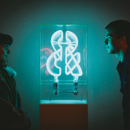 Students observe a neon sculpture on view at the Neuberger Museum of Art.