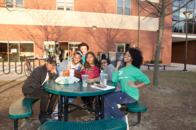 Students outside eating at a table