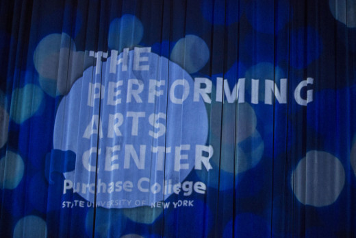 The PAC logo projected on the PepsiCo Theatre's stage curtain.