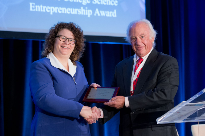 Judith Dunn accepts the 2017 Purchase College Science Entrepreneurship Award at the Health Tech Conference in Tarrytown, New York, presented by President Thomas Schwarz.