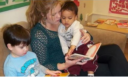 Woman reading a book to two children