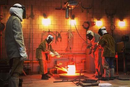 Students dressed in protective gear, forging metal in a metal foundry on campus.