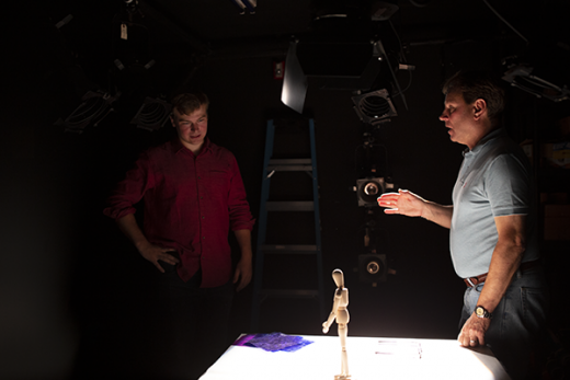 David Grill '86 and student look at stage model