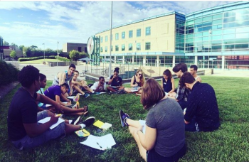 Students working on a group project on the lawn.