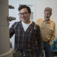 Professor Jan Factor works with a student on electron microscope