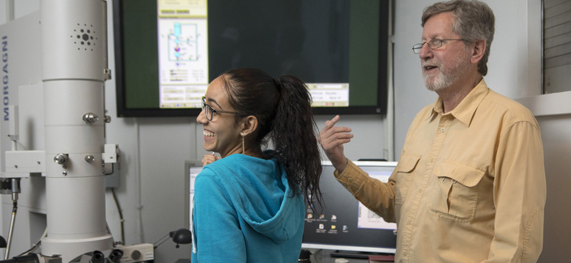 Student in blue sweatshirt smiles using an electron microscope while smiling professor looks on.