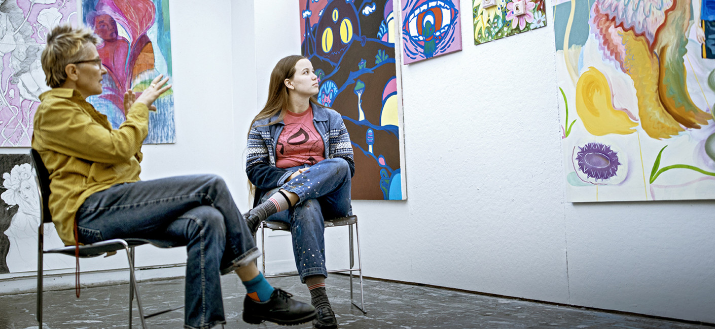 A professor and a student sit together viewing and discussing paintings hung on a wall.