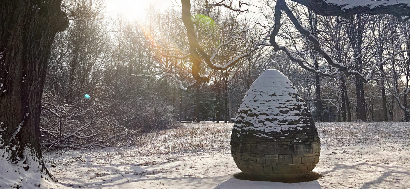 Egg shaped sculpture made of stone bricks sits under the branch of a tree with a dusting of snow on top and all around.