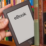 eBook reader is being shelved next to print books.