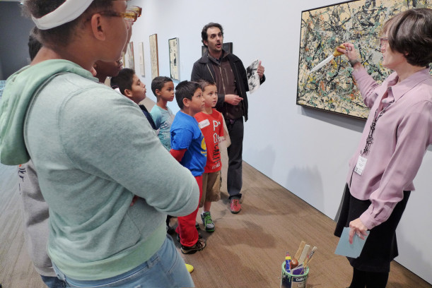 Docent Nancy Drain explains Jackson Pollock's painting techniques to kids from the Don Bosco center and to Leandro Benmergui, director of Casa Purchase.