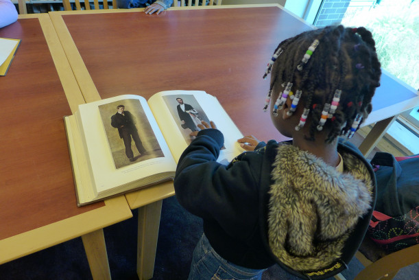 Jordin Faison, 7, From Port Chester examines and art book in the Library.